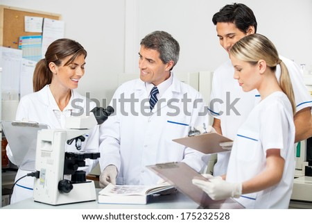 Mature male researcher with students taking notes in medical laboratory - stock photo