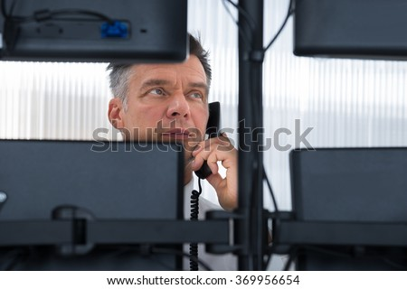 Mature male stock trader using telephone while looking at multiple computer screens at office - stock photo