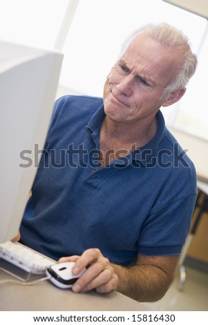 Mature male student frowning at computer monitor - stock photo