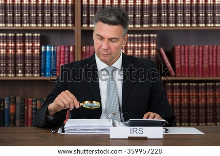 Mature male tax auditor examining documents with magnifying glass at table in office - stock photo