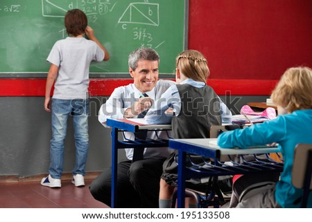 Mature male teacher looking at little schoolgirl while crouching at desk in classroom - stock photo