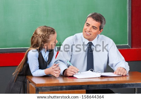 Mature male teacher looking at schoolgirl against chalkboard in classroom - stock photo