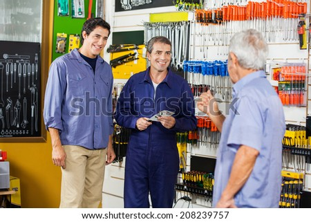 Mature male worker with customers standing in hardware shop