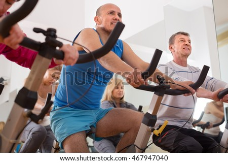 mature males on exercise bikes in the gym