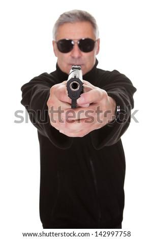Mature man aiming towards camera over white background - stock photo
