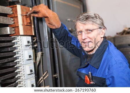 Mature man an electrician turning on circuit breaker in panel - stock photo