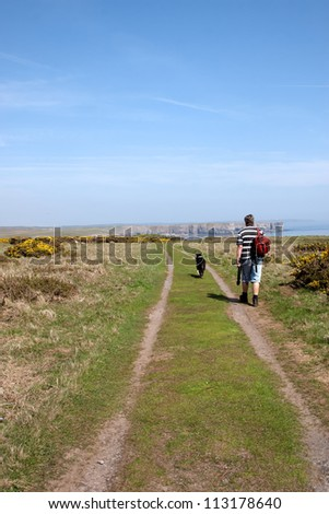 Mature man and his dog walking the coastal path - stock photo
