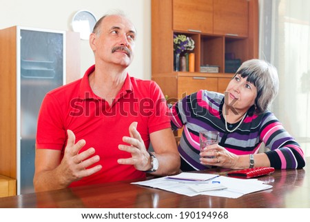 Mature man and woman having financial problems at home - stock photo