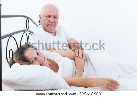 Mature man and woman on   bed in   bedroom.