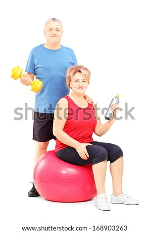 Mature man and woman posing with exercising equipment isolated against white background