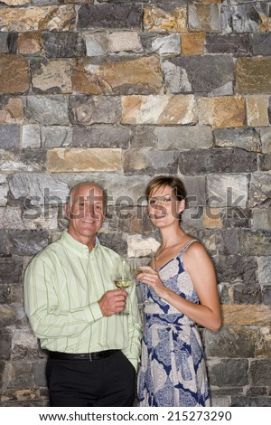 Mature man and young woman standing beside stone wall, holding glasses of white wine, smiling, portrait - stock photo
