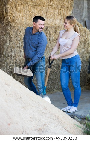 Mature man and young woman standing with metallic spades in hangar with sand pile