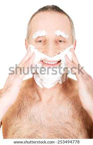 Mature man applying shaving foam.