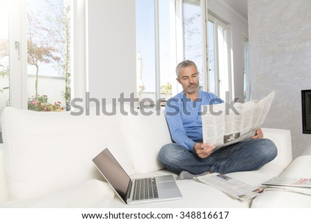 Mature man at home, sitting on couch, reading newspaper