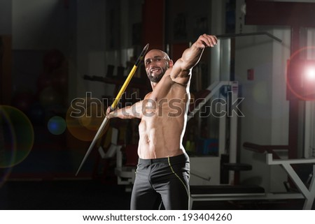 Mature Man Athlete Practicing To Throw A Javelin - stock photo