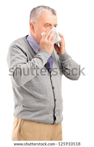 Mature man blowing his nose in a tissue isolated on white background - stock photo