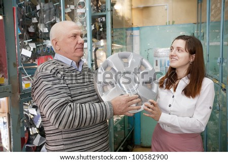 mature man buys automotive wheel covers in the auto parts store - stock photo