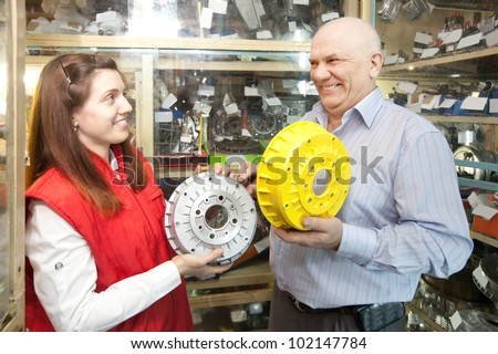 mature man buys brake wheel in auto parts store