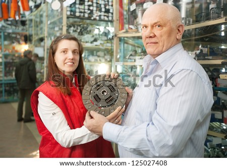 mature man buys engine clutch in auto parts store - stock photo