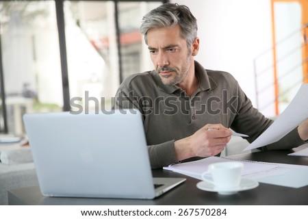 Mature man calculating budget on laptop - stock photo