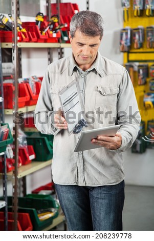 Mature man checking product through digital tablet in hardware store - stock photo