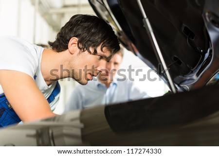 Mature man - client - and young mechanic are looking beneath a hood with a lamp - stock photo