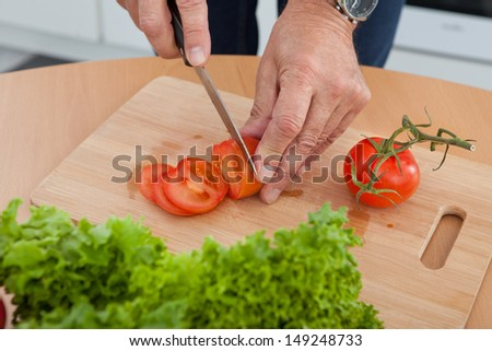 Mature Man Cutting Vegetable In The Kitchen