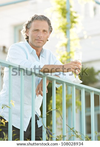 Mature man drinking champagne whilst leaning on a balcony. - stock photo
