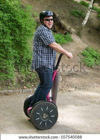 Mature man driving on segway - stock photo