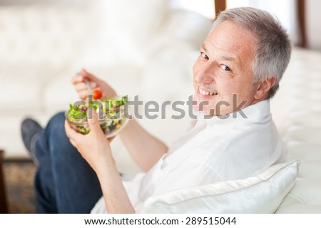 Mature man eating a healthy salad sitting on his couch - stock photo