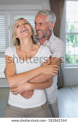 Mature man embracing smiling woman from behind at home