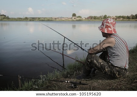 Mature man fishing on coast of a pond at sunset - stock photo