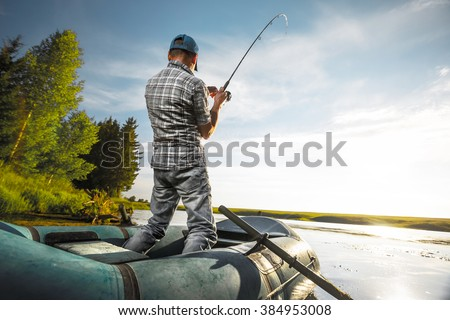 Mature man fishing on the lake from inflatable boat - stock photo