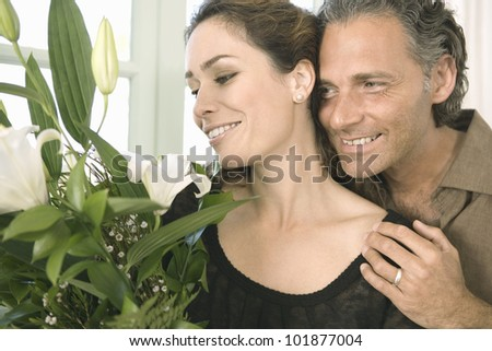 Mature man giving  a woman a bunch of flowers at home. - stock photo