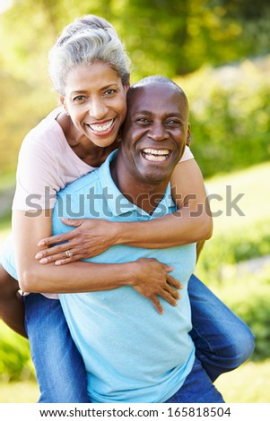 Mature Man Giving Woman Piggyback In Countryside - stock photo