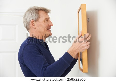 Mature Man Hanging Picture On Wall - stock photo