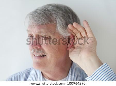 mature man has trouble hearing - stock photo