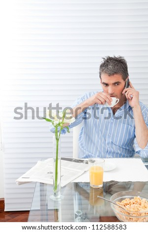 Mature man having breakfast using phone.