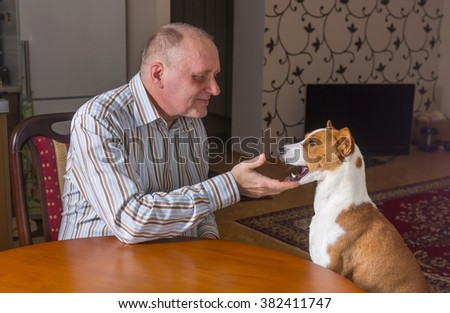 Mature man having conversation with basenji dog sitting at the table