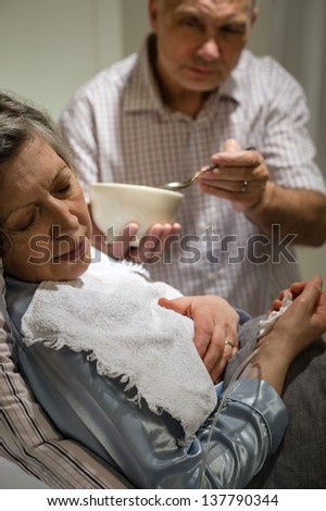 Mature man helping his ill wife feeding soup - stock photo
