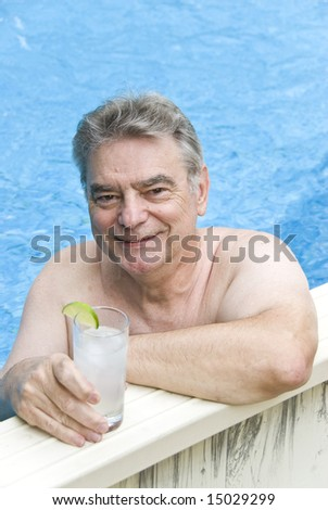 Mature Man Holding a Gin and Tonic Posing in a Swimming Pool