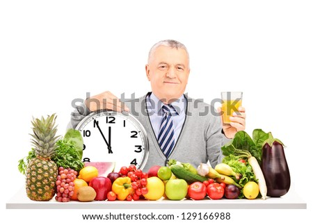 Mature man holding an orange juice with clock, fruit and vegetables on a table isolated on white background - stock photo