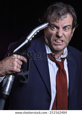 Mature man holding fuel dispenser near his temple. Isolated on black - stock photo