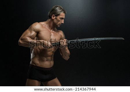 Mature Man Holding Sword Ready To Fight - Portrait Of A Handsome Muscular Ancient Warrior With A Sword - stock photo
