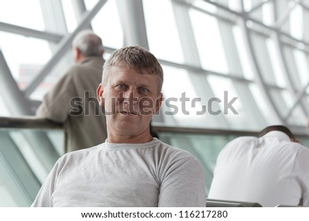mature man in a waiting room of the international airport - stock photo