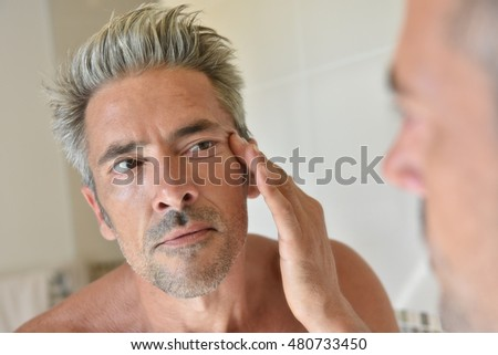 Mature man in front of mirror applying cream