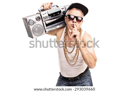 Mature man in hip-hop clothes carrying a ghetto blaster over his shoulder and holding a finger on his lips isolated on white background