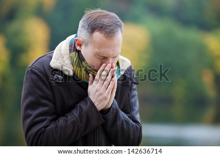 Mature man in jacket suffering from cold - stock photo