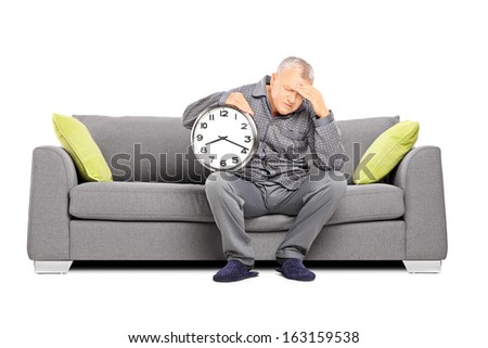 Mature man in pajamas seated on a sofa holding a clock and having a headache isolated on white background - stock photo