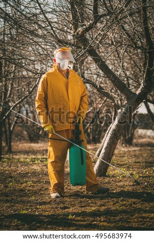 Mature man in protection suit spraying tree with chemicals in the orchard before winter.